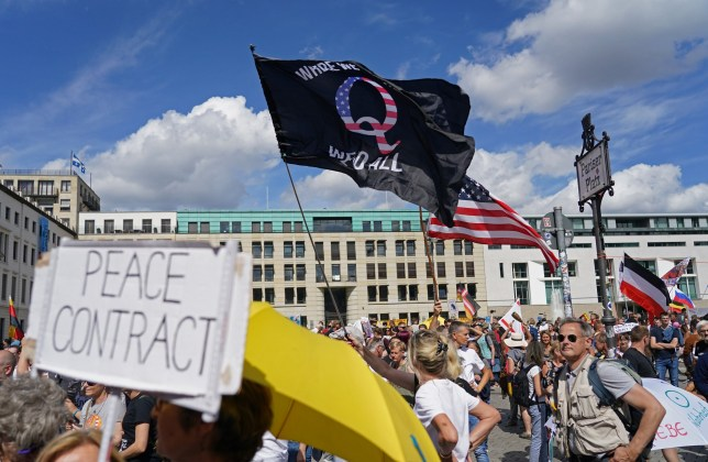 A man waves a QAnon conspiracy flag at a protest of coronavirus skeptics, right-wing extremists and others angry over coronavirus-related restrictions and government policy on August 29 in Berlin