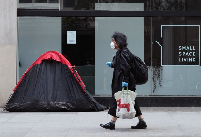 File photo dated 15/5/2020 of a woman walking past a homeless person's tent erected outside a furniture store in Tottenham Court Road, London. A winter homelessness crisis can only be averted if the ban on evictions in the aftermath of the coronavirus outbreak is extended, Labour has said. PA Photo. Issue date: Friday September 18, 2020. The party's shadow housing secretary Thangam Debbonaire said the Government needed to do more to help renters. Ms Debbonaire called for protection measures to be extended. See PA story HEALTH Coronavirus. Photo credit should read: Yui Mok/PA Wire