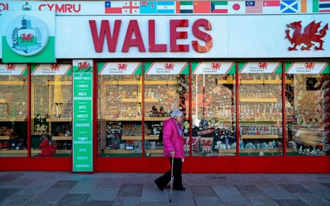 A woman walks past a souvenir shop in Cardiff