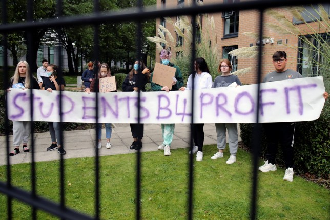 Students hold a placard as they protest outside Birley Halls at Manchester Metropolitan University