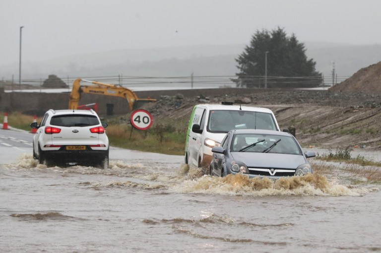 Cars make their way through a flooded road in Claudy, County Londonderry. The UK's wet weekend will continue as a weather warning for rain across parts of Wales and England has been extended. PA Photo. Picture date: Sunday October 4, 2020. Some places in Somerset and Hampshire have had more than a month's worth of rainfall in 42 hours, as the Met Office issued warnings not seen since March. See PA story WEATHER Rain. Photo credit should read: Niall Carson/PA Wire