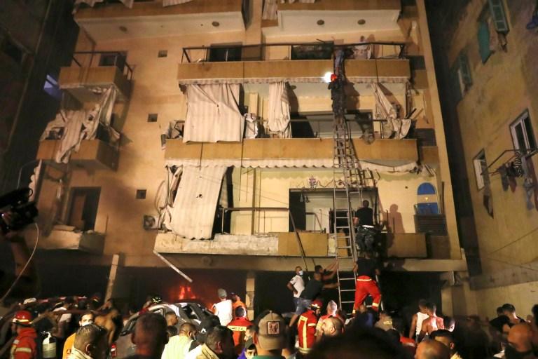 Des personnes sont évacuées par les pompiers de leurs appartements après l'explosion d'un réservoir d'essence dans le quartier de Tarik al-Jadida, à Beyrouth, au Liban, le vendredi 9 octobre 2020.