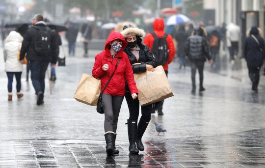 Women wearing face masks carry shopping bags amid the outbreak of the coronavirus disease (COVID-19) in Liverpool, Britain, October 12, 2020. REUTERS/Phil Noble