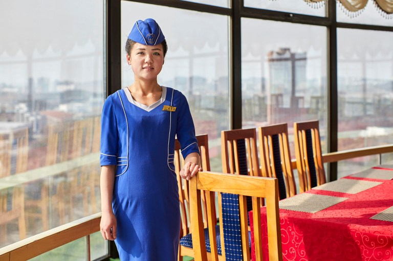 hotels of pyongyang book captures hotel interiors and staff in north korea's capital city: staff member preparing for dinner service