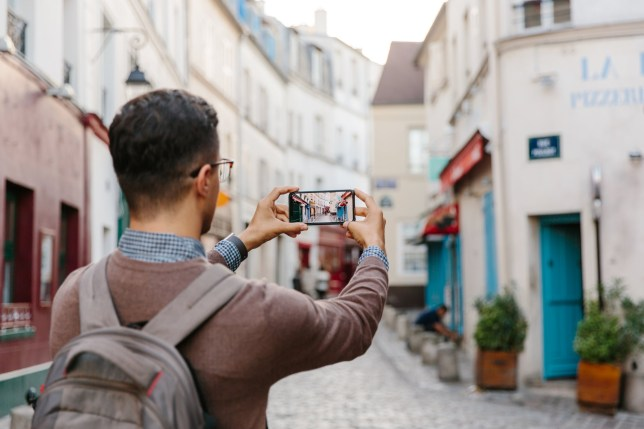 Rear view of a young man taking pictures of Montmartre street with smart phone, Paris, France