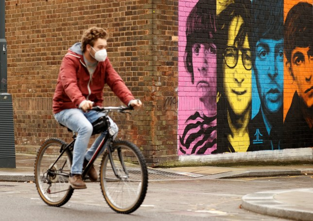 A man wearing a protective mask rides a bike past a mural depicting members of The Beatles.