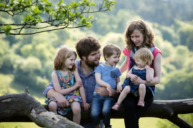 A mother and father can be seen sitting on a branch with their three children