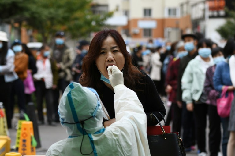 A medical worker in protective suit collects a swab from a woman for nucleic acid testing, following new cases of coronavirus disease (COVID-19) in Qingdao, Shandong province, China October 13, 2020. Picture taken October 13, 2020. China Daily via REUTERS ATTENTION EDITORS - THIS IMAGE WAS PROVIDED BY A THIRD PARTY. CHINA OUT.