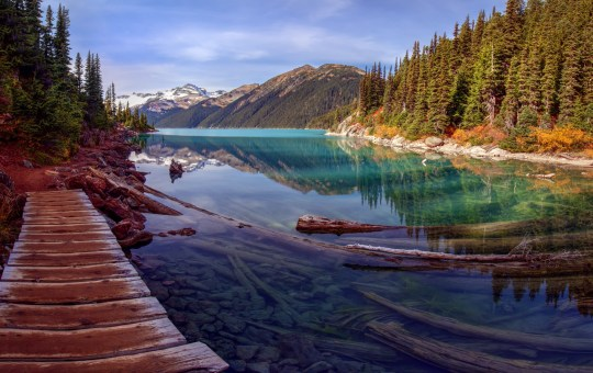Picturesque path along turquoise mountain lake with a pine tree lined shore and snow capped mountains in the background; Shutterstock ID 325691804; Department: -