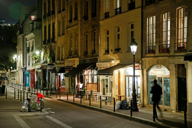 PARIS, FRANCE - OCTOBER 14: A man walks in a deserted street as French President Emmanuel Macron deploys curfew amid accelerating coronavirus epidemic on October 14, 2020 in Paris, France. French President Emmanuel Macron announced on television this evening a curfew for Ile-de-France and eight metropolises between 9 p.m. and 6 a.m. on Saturday to tackle a second wave of the coronavirus outbreak across France. Bars and restaurants in Paris and the inner suburbs will close their doors at 9 p.m. from October 17, for a period of one month. (Photo by Chesnot/Getty Images)
