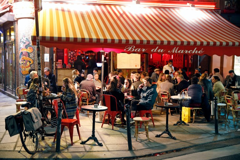 PARIS, FRANCE - OCTOBER 14: People enjoy a drink in a cafe terrace as French President Emmanuel Macron deploys curfew amid accelerating coronavirus epidemic on October 14, 2020 in Paris, France. French President Emmanuel Macron announced on television this evening a curfew for Ile-de-France and eight metropolises between 9 p.m. and 6 a.m. on Saturday to tackle a second wave of the coronavirus outbreak across France. Bars and restaurants in Paris and the inner suburbs will close their doors at 9 p.m. from October 17, for a period of one month. (Photo by Chesnot/Getty Images)