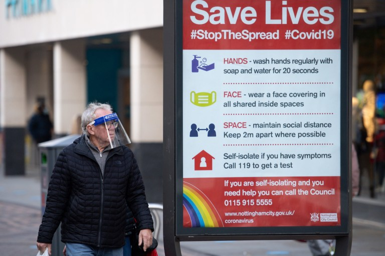 A man wearing a face shield walks past a coronavirus advice sign in Nottingham city centre. Nottinghamshire has been placed into Tier 2 of the new coronavrius restrictions with meeting socially banned indoors and the rule of six applying outdoors. PA Photo. Picture date: Thursday October 15, 2020. Prime Minister Boris Johnson set out a new three-tier system of alert levels for England following rising coronavirus cases and hospital admissions. See PA story HEALTH Coronavirus. Photo credit should read: Jacob King/PA Wire