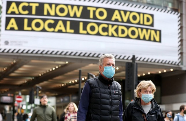 People wearing face masks walk past a advertisement on Market Street in Manchester