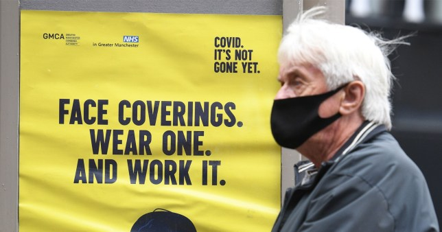 A man wearing a facemask walks past a poster urging people to wear face coverings.