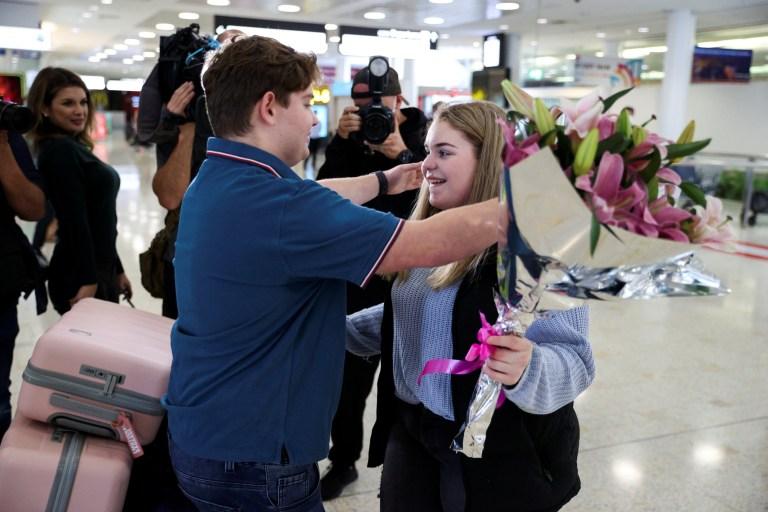 Une personne embrasse sa petite amie alors qu'elle arrive de Nouvelle-Zélande après l'ouverture de la bulle de voyage Trans-Tasman pendant la nuit