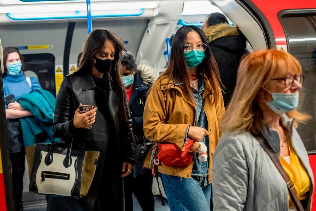 Commuters in face masks on the Tube