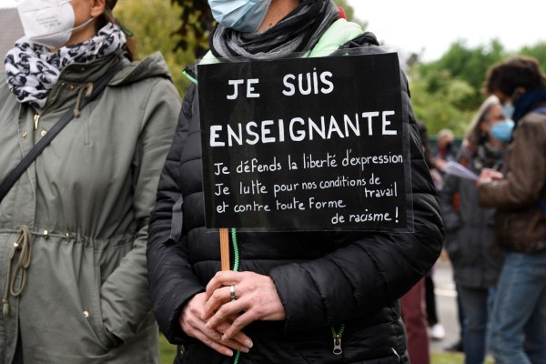 A teacher stands with a placard reading 'I am a teacher, I defend the freedom of speech, I fight for our work conditions and against all kind of racism' near the entrance of a middle school in Conflans-Sainte-Honorine, 30kms northwest of Paris, on October 17, 2020, after a teacher was decapitated by an attacker who has been shot dead by policemen. - The man suspected of beheading on October 16 ,2020 a French teacher who had shown his students cartoons of the prophet Mohammed was an 18-year-old born in Moscow and originating from Russia's southern region of Chechnya, a judicial source said on October 17. Five more people have been detained over the murder on October 16 ,2020 outside Paris, including the parents of a child at the school where the teacher was working, bringing to nine the total number currently under arrest, said the source, who asked not to be named. The attack happened at around 5 pm (1500 GMT) near a school in Conflans-Sainte-Honorine, a western suburb of the French capital. The man who was decapitated was a history teacher who had recently shown caricatures of the Prophet Mohammed in class. (Photo by Bertrand GUAY / AFP) (Photo by BERTRAND GUAY/AFP via Getty Images)