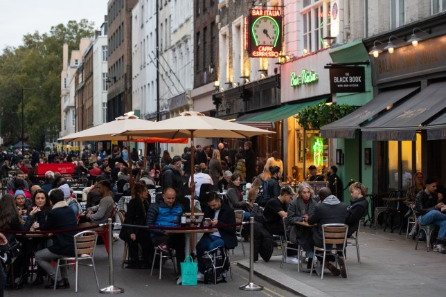 People eat and drink outside bars and restaurants in Soho, London