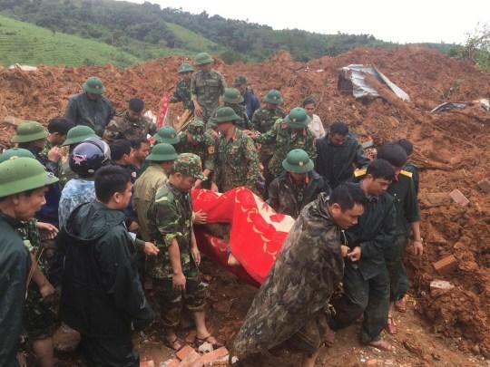 Des officiers de l'armée portent un corps récupéré d'un glissement de terrain dans la province de Quang Tri, au Vietnam, dimanche 18 octobre 2020. Le glissement de terrain dans le centre du Vietnam a enterré au moins 22 officiers de l'armée, juste une semaine après un autre glissement de terrain tué plus d'une douzaine d'autres en raison de pluies dans la région, ont rapporté les médias officiels.  (Tran Le Lam / VNA via AP)