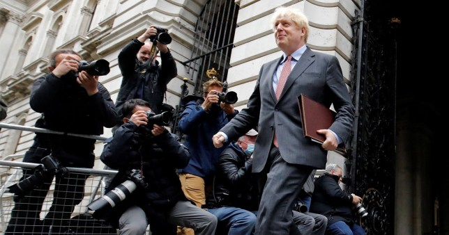 Prime Minister Boris Johnson passes photographers as he returns to Downing Street after attending a weekly cabinet meeting
