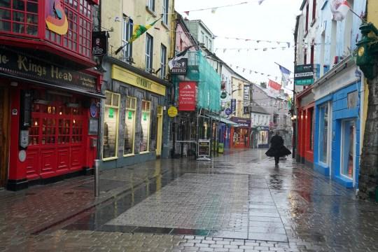 Une femme se promène dans une rue commerçante vide du centre-ville alors que l'épidémie de coronavirus (COVID-19) se poursuit, à Galway, en Irlande, le 19 octobre 2020.