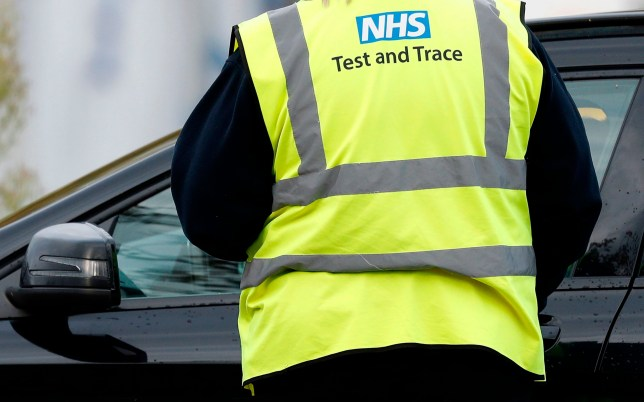 A worker wearing a high-vis jacket with an NHS Test and Trace logo on, advises drivers attending a novel coronavirus COVID-19 drive-in testing facility set up at the Chessington World of Adventures Resort, in Chessington, southwest of London, on October 20, 2020. - British Prime Minister Boris Johnson, who was criticised for acting too slowly earlier in the year, favours a strategy of localised lockdowns in England to avoid worsening the historic recession sparked by the outbreak. (Photo by Adrian DENNIS / AFP) (Photo by ADRIAN DENNIS/AFP via Getty Images)