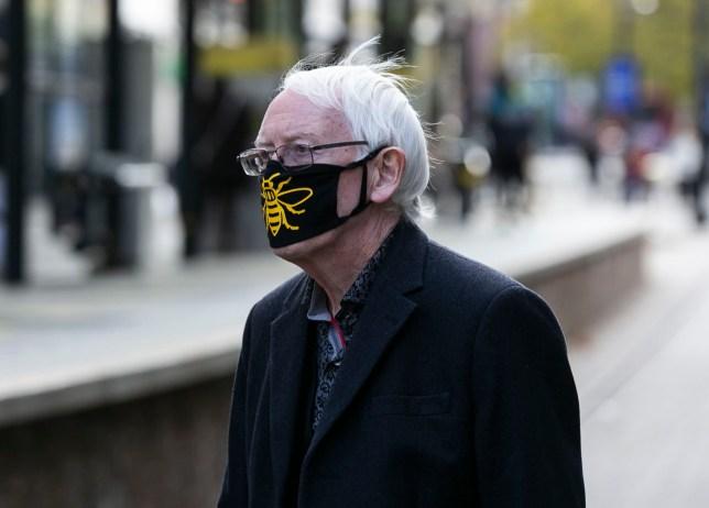 An elderly man walks through Manchester with a Manchester bee face mask on