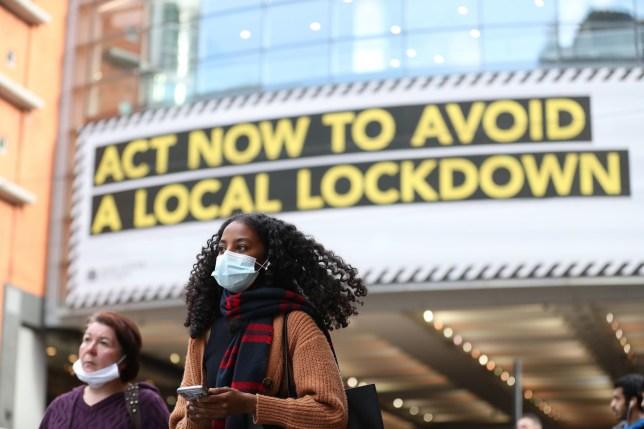 A woman wearing a face mask walks through Manchester