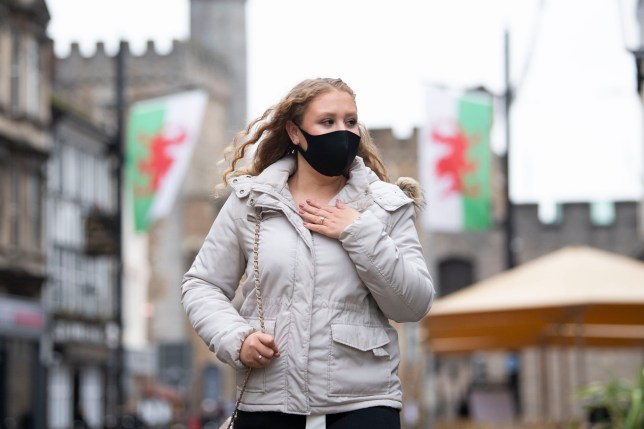 Woman wearing a face mask walks past Welsh flags.