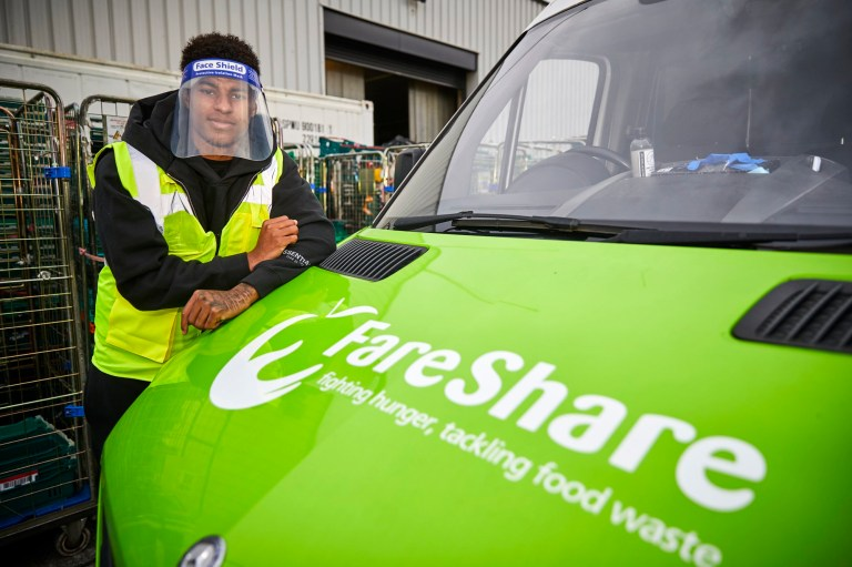 Manchester United player Marcus Rashford wearing a face visor and high vis jacket while leaning on the bonnet of a FareShare van