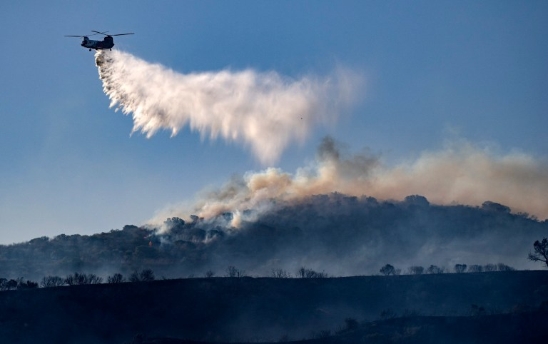 A helicopter drops retardant on the Silverado wildfire off Santiago Canyon Road where fierce winds have cause problems on Monday, Oct. 26, 2020, in Irvine, California.