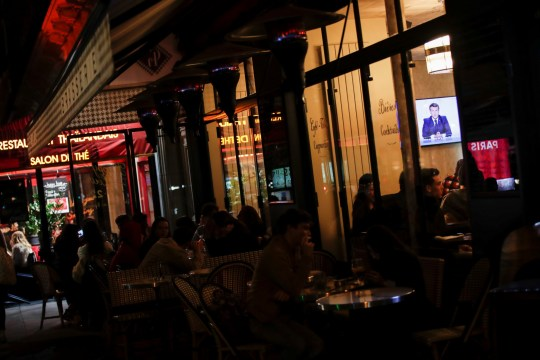 People watch French President Emmanuel Macron on a TV screen in a restaurant in Paris