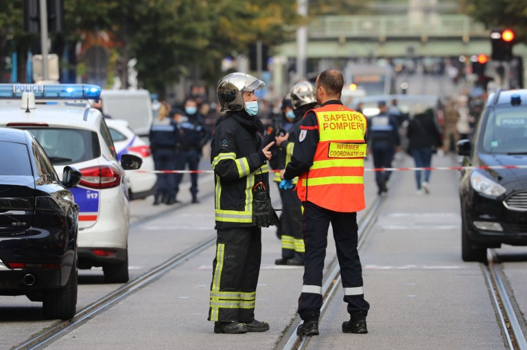 French policemen and firefighters stand guard a street after a knife attack in Nice on October 29, 2020. - A man wielding a knife outside a church in the southern French city of Nice slit the throat of one person, leaving another dead and injured several others in an attack on Thursday morning, officials said. The suspected assailant was detained shortly afterwards, a police source said, while interior minister Gerald Darmanin said on Twitter that he had called a crisis meeting after the attack. (Photo by Valery HACHE / AFP) (Photo by VALERY HACHE/AFP via Getty Images)