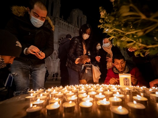 People pay tribute in front of the Notre Dame Basilica