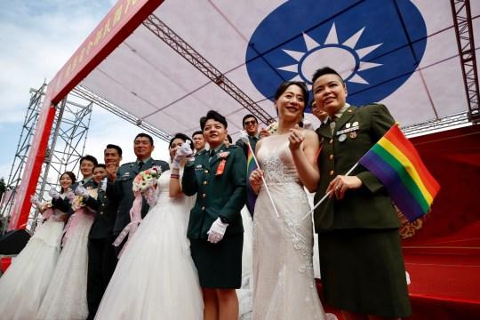 epa08784992 (R à L) Couples Yi Wang et Yumi Meng, Ying-Hsuan Chen et Li-Chen Li posent pour une photo à côté d'autres couples militaires lors d'un mariage de masse militaire à Taoyuan, Taiwan, le 30 octobre 2020. Deux couples de même sexe attachés le nœud dans le cadre d'un mariage de masse organisé par l'armée taïwanaise.  Selon les médias, c'est la première fois que des couples de même sexe se marient dans le cadre d'un mariage de masse organisé par l'armée depuis que Taiwan est devenu le premier pays d'Asie à légaliser le mariage homosexuel en mai 2019. EPA / RITCHIE B. TONGO
