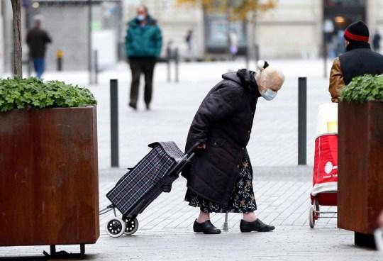 Une vieille femme, portant un masque facial à titre préventif contre le coronavirus (COVID-19), marche dans une rue alors que la Belgique impose de nouvelles mesures régionales contre le COVID-19