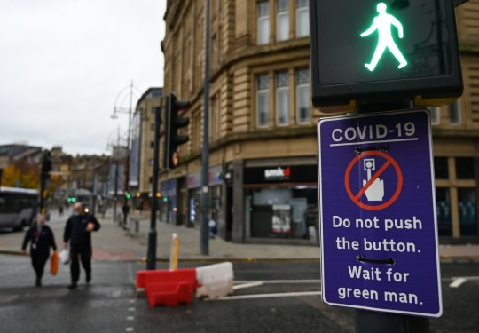 Pedestrians pass a sign displaying a COVID-19 sign advising pedestrians not to use the button, is displayed on a traffic light pole in the centre of Bradford, west Yorkshire on October 31, 2020, as the number of cases of the novel coronavirus COVID-19 rises. - British Prime Minister Boris Johnson is considering imposing a new lockdown across England within days following warnings his localised restrictions strategy has failed to curb soaring coronavirus rates, reports said Saturday. (Photo by Paul ELLIS / AFP) (Photo by PAUL ELLIS/AFP via Getty Images)