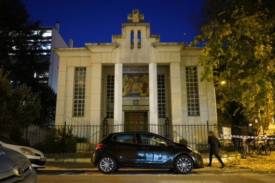 A woman walks past the Greek Orthodox church after a priest was shot