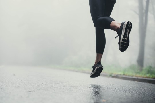 Unrecognizable athlete jogging on the road during rainy day.