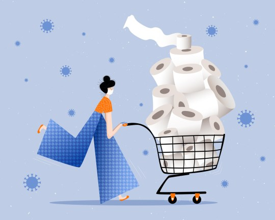 Woman wearing face mask and surgical gloves panic buying full shopping cart of toilet paper during the coronavirus crisis.