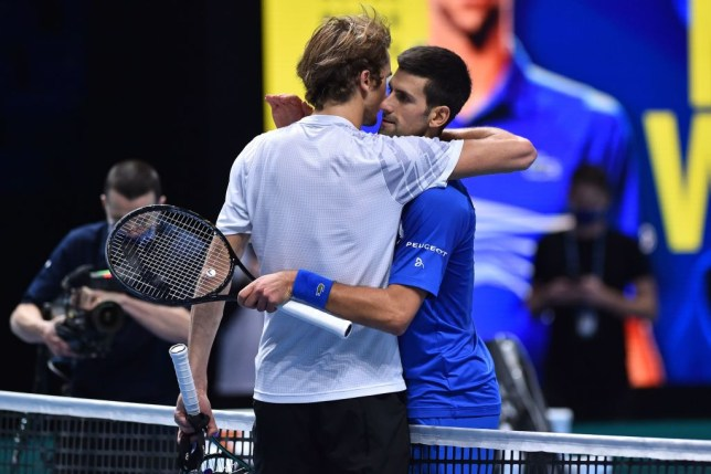 Serbia's Novak Djokovic (R) embraces Germany's Alexander Zverev (L) after his victory in straight sets in their men's singles round-robin match on day six of the ATP World Tour Finals tennis tournament at the O2 Arena in London on November 20, 2020.