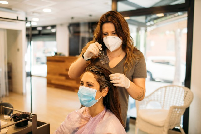 Female hairdresser with mask staining hair of female customer with mask