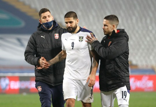Mitrovic is consoled by Serbia team-mates after their defeat to Scotland