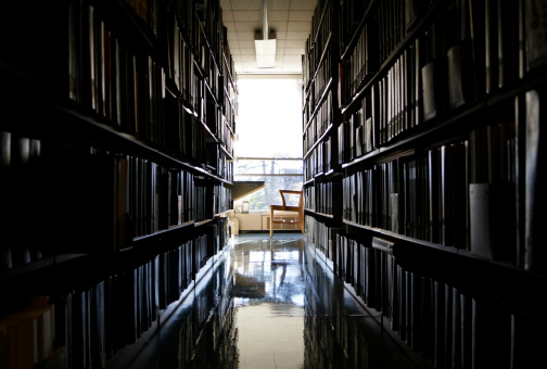 A quiet, secluded workplace at a university library, dark before stark bright light coming in through a window.