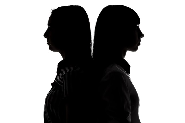Silhouette of sisters standing back-to-back