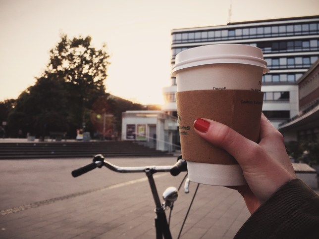 Cropped Image Of Woman Hand Holding Disposable Coffee Cup On City Street