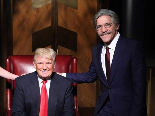 Donald Trump sitting on a red leather chair smiling as a talk show host with a grey moustache, hair and glasses places a hand on his shoulder