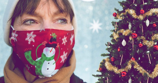 A woman wears a Christmas themed face mask next to a decorated Christmas tree
