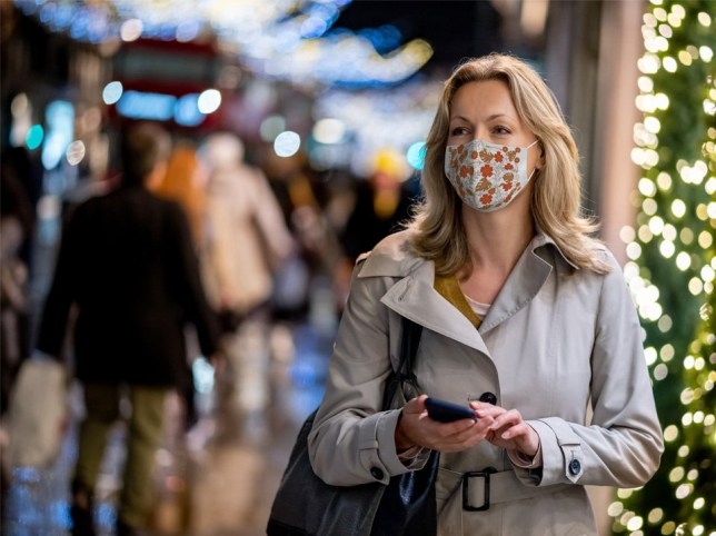 A woman wearing a face mask in front of Christmas lights