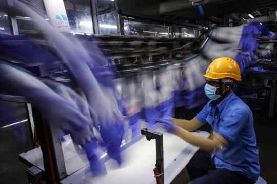 epa08774416 FINANCEMENT DES ENTREPRISES DE L'ÉCONOMIE ANNÉE 2020 Une image réalisée avec une longue exposition montre un travailleur inspectant des gants à l'intérieur de l'usine Top Glove à Setia Alam, à l'extérieur de Kuala Lumpur, Malaisie, le 6 octobre 2020. Top Glove est le plus grand fabricant de gants en caoutchouc au monde.  EPA / FAZRY ISMAIL
